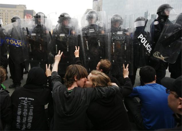 Toronto 2010. Due attivisti si fermano a baciarsi davanti al cordone della polizia. AP/LaPresse.