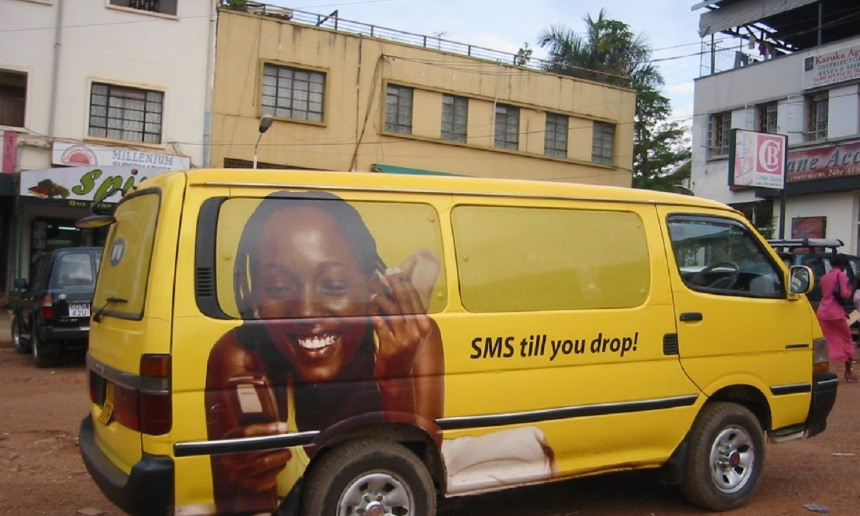 %22SMS till you drop%22 -- mobile phone ad on van in Kampala, Ugand